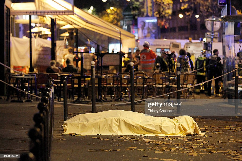 A victim's body lies covered on Boulevard des Filles du Calvaire, close to the Bataclan theater, early on November 14, 2015 in Paris, France. According to reports, over 150 people were killed in a series of bombings and shootings across Paris, including at a soccer game at the Stade de France and a concert at the Bataclan theater.