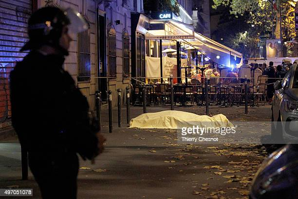 Victim's body lies covered on Boulevard des Filles du Calvaire, close to the Bataclan theater, early on November 14, 2015 in Paris, France. According...