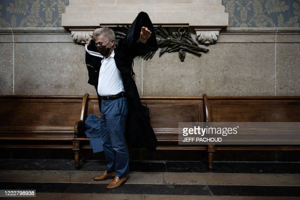 Victims lawyer Christophe Leguevaques puts on his robe at the courthouse of Lyon centraleastern France on June 25 during the ruling in the appeal...