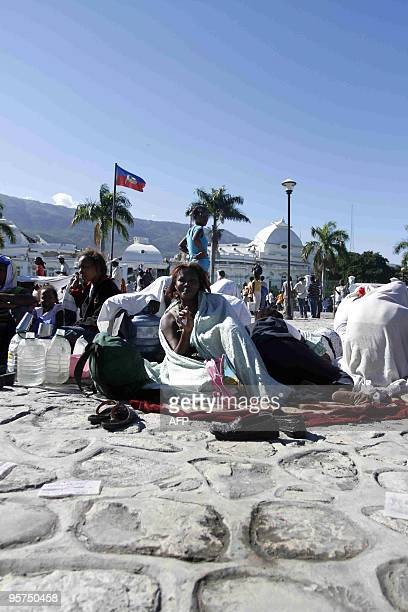 Victims of a massive earthquake rest in a sqaure in PortauPrince on January 13 2010 Planeloads of rescuers and relief supplies headed to Haiti as...