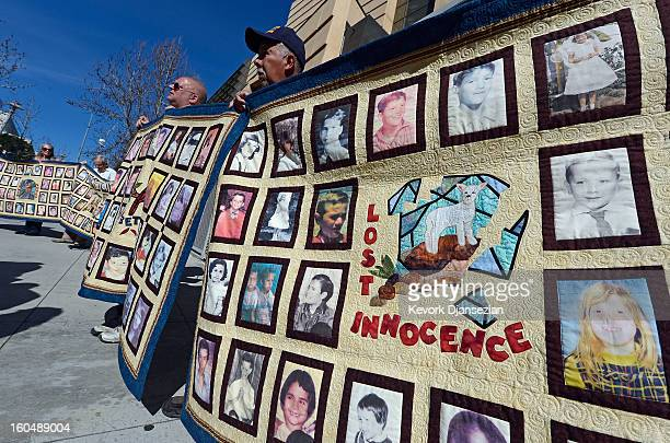 Victims of alleged sexual abuse by priests in the Catholic Archdiocese of Los Angeles hold up quilts with pictures of other alleged victims during a...
