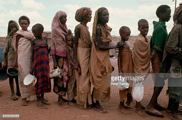 Victims of famine wait in line for food during Somalia's civil war In the 1980s warlord factions joined together to overthrow then president Siad...