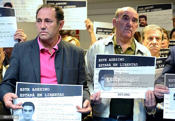 Victims of terrorism hold placards with pictures of members of the Basque separatist group ETA and reading This murderer will be free during a press...