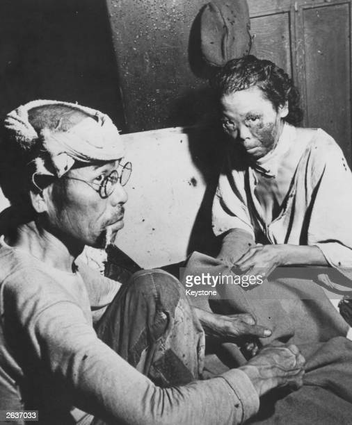 Victims of the atomic blast sit in a makeshift hospital in a damaged bank building in the centre of Hiroshima