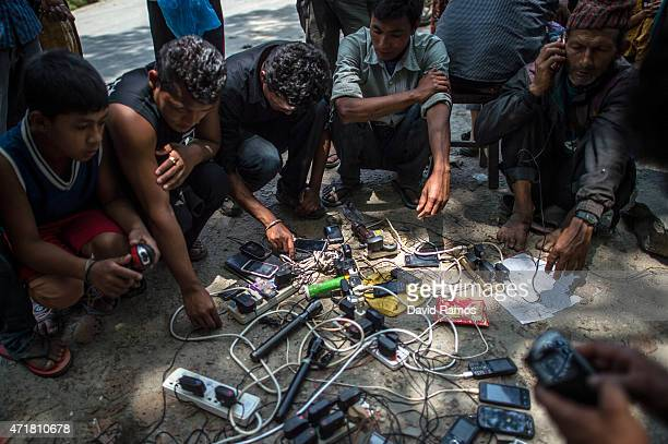 Victims of the earthquake charge their mobile phones on the street on May 1 2015 in Melamchi Nepal A major 78 earthquake hit Kathmandu midday on...