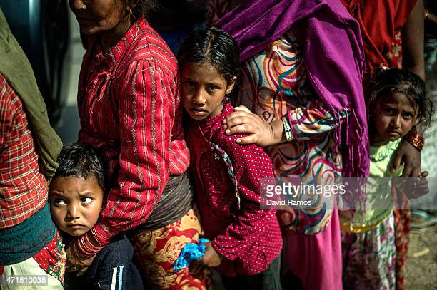 Victims of the earthquake queue on a road as they wait to receive food and goods at an aid distribution point on May 1 2015 in Bhotechaur Nepal A...