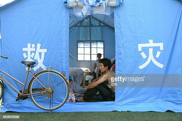 Victims of the massive explosions sit in a tent in a temporary shelter at an elementary school in Tianjin on August 13 2015 Enormous explosions in a...
