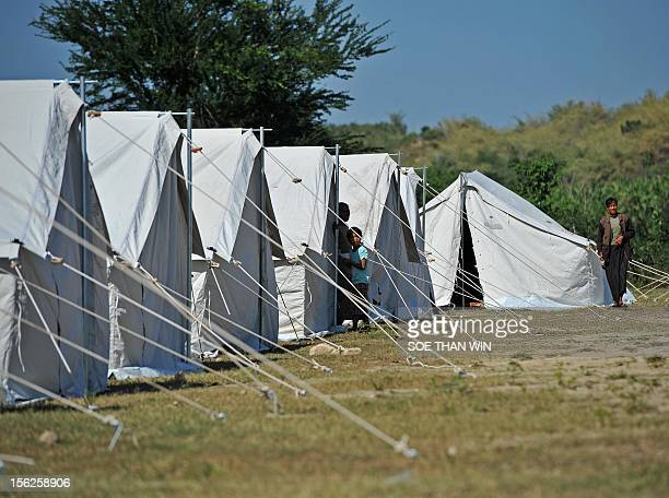 Victims of the recent earthquake stand outside tents at a camp in Thabeik Kyintownship Mandalay a division in central Myanmar on November 12 2012...