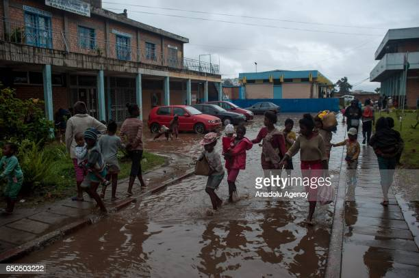 Victims of the tropical cyclone Enawo head to a sports hall to shelter in Antananarivo Madagascar on March 9 2017 Red Cross staff gave food aid to...