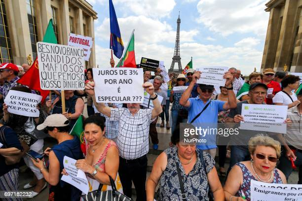 Victims of toxic investments made by former Banco Espirito Santo now Novo Banco hold posters and shout slogans in front of the Eiffel tower in Paris...