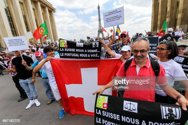 Victims of toxic investments made by former Banco Espirito Santo now Novo Banco hold a Swiss flag in front of the Eiffel tower in Paris on June 17...