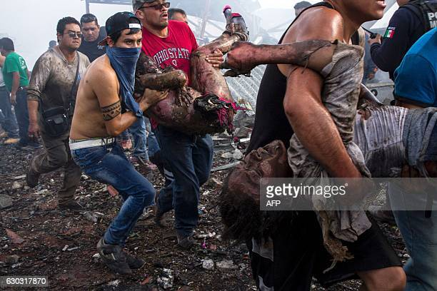 TOPSHOT Victims severely burned are taken away by rescuers from the smoldering ruins of a fireworks market flattened by a huge blast that killed at...