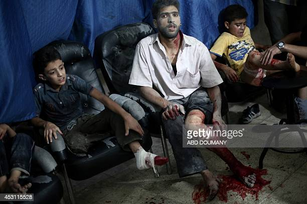 Victims wait to be treated by medics at a makeshift hospital following reported shelling by Syrian government forces in Douma northeast of Damascus...