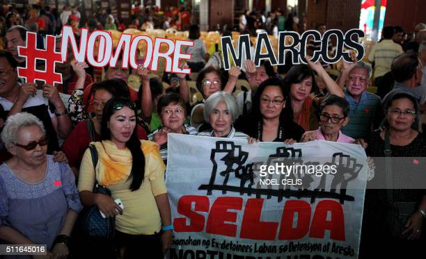 Victims who endured torture and imprisonment during late Philippine dictator Ferdinand Marcos' twodecadelong reign raise their fists in the air and...