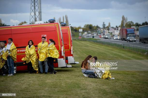 Victims wrapped in survival blankets stands by ambulances during an exercise simulating a terrorist attack inside the theatre Espace Malraux in...