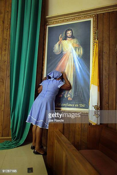 Victoire Lordeus leans against a painting of Jesus as she says goodbye to the Divine Mercy Haitian Mission during a closing ceremony on September 30...