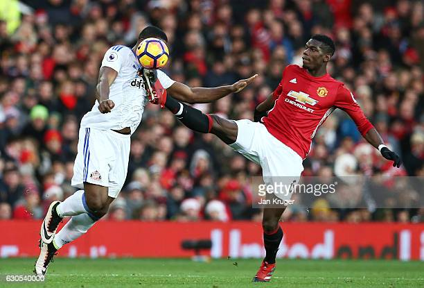 Victor Anichebe of Sunderland and Paul Pogba of Manchester United compete for the ball during the Premier League match between Manchester United and...
