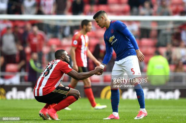 Victor Anichebe of Sunderland shakes hands with Marcos Rojo of Manchester United after the Premier League match between Sunderland and Manchester...
