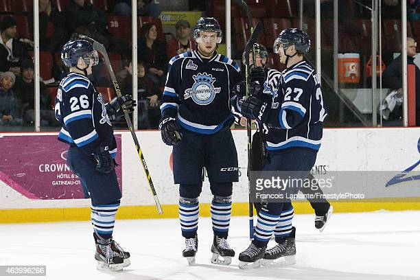 Victor Baldaev of the Chicoutimi Sagueneens celebrates his third period goal with teammates Jeremy Bouchard and Laurent Dauphin in a game against the...