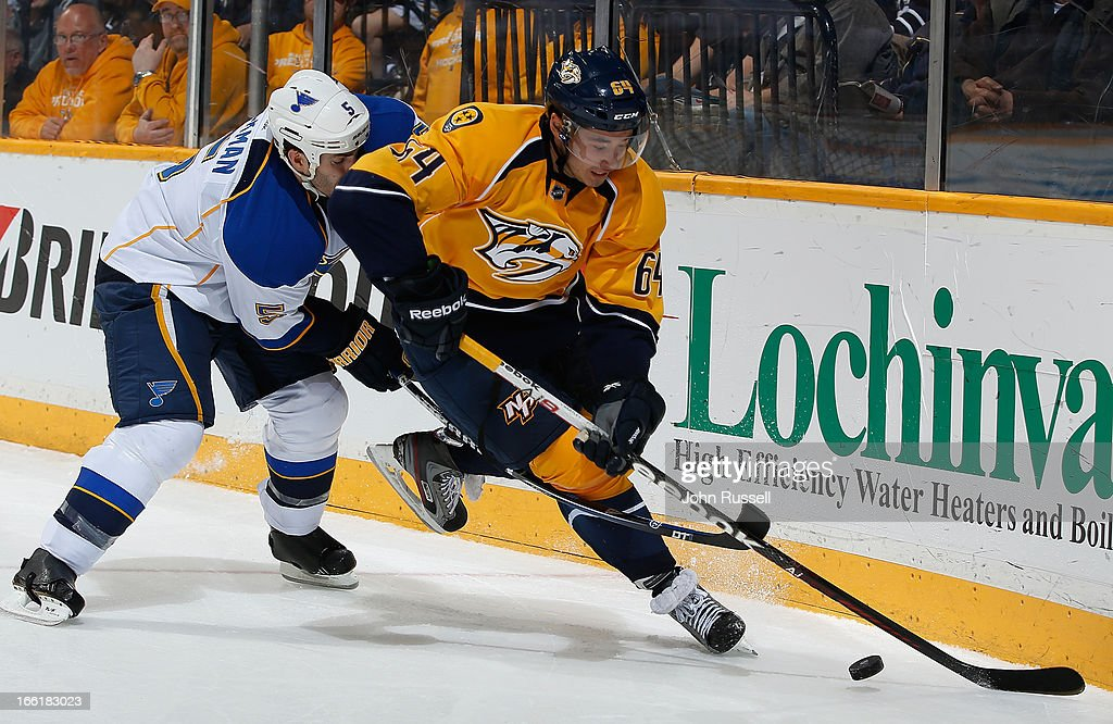 Victor Bartley #64 of the Nashville Predators battles along the boards against Barret Jackman #5 of the St. Louis Blues during an NHL game at the Bridgestone Arena on April 9, 2013 in Nashville, Tennessee.