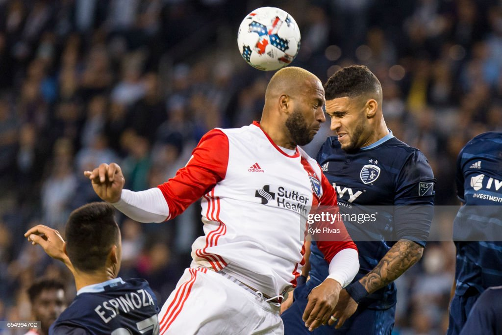 Victor Bernardez #5 of San Jose Earthquakes attempts to head a shot on goal past Dom Dwyer #14 and Ike Opara #3 of Sporting Kansas City in stoppage time at Children's Mercy Park on March 18, 2017 in Kansas City, Kansas.