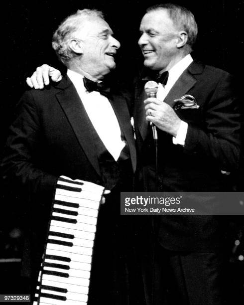 Victor Borge holding piano keyboard scarf frolics with Frank Sinatra on stage at Radio City Music Hall
