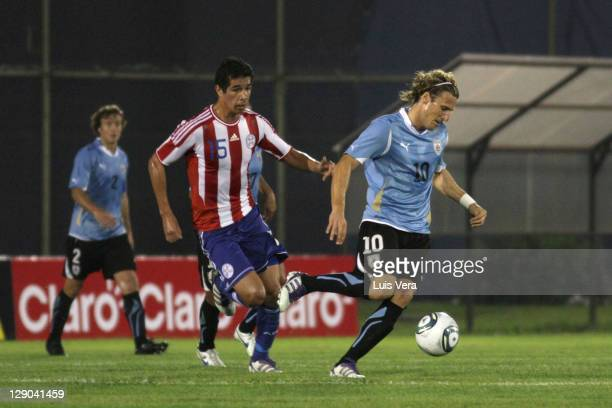 Victor Caceres of Paraguay fights for the ball with Diego Forlan of Uruguay during the match between Paraguay and Uruguay as part of the first round...