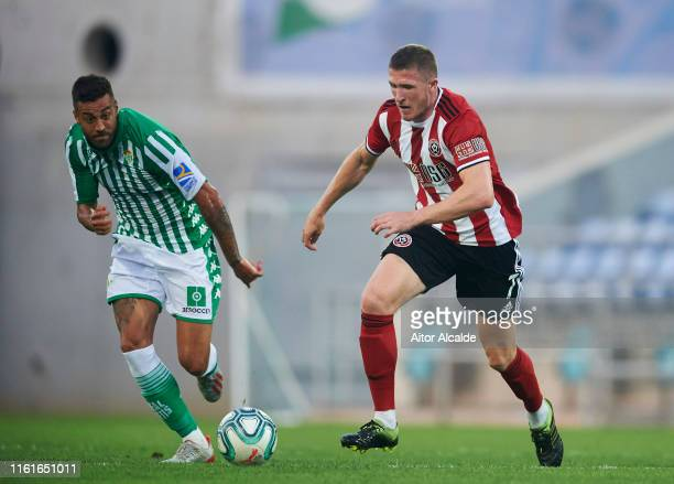 Victor Camarasa of Real Betis Balompie duels for the ball with John Lundstram of Sheffield United during a preseason friendly match between Real...