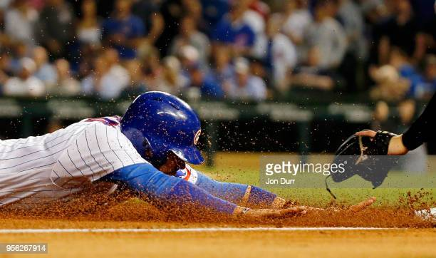 Victor Caratini of the Chicago Cubs slides safely into third base against the Miami Marlins during the sixth inning at Wrigley Field on May 8 2018 in...