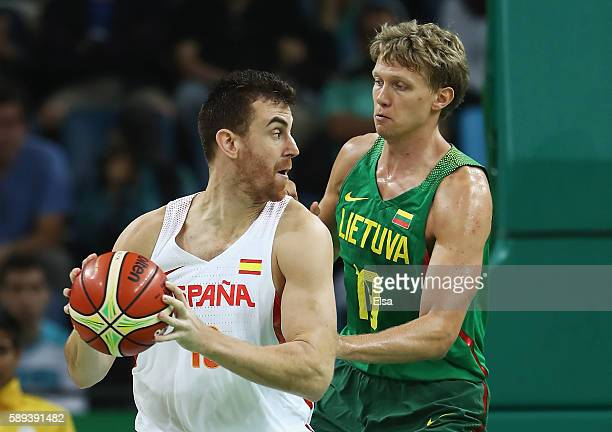 Victor Claver of Spain controls the ball against Mindaugas Kuzminskas of Lithuania during the Men's Preliminary Round Group B between Spain and...