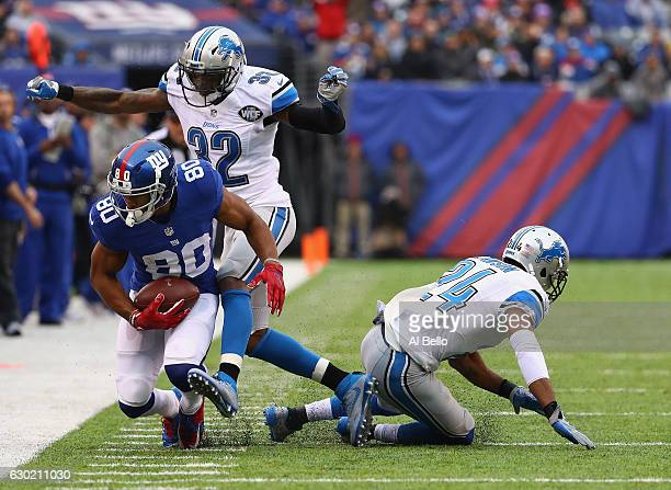 Victor Cruz of the New York Giants carries the ball against Tavon Wilson and Nevin Lawson of the Detroit Lions in the first half at MetLife Stadium...