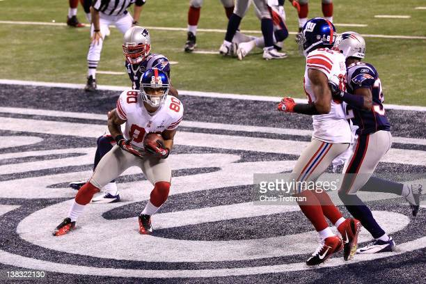 Victor Cruz of the New York Giants catches a two yard touchdown pass from Eli Manning in first quarter against the New England Patriots during Super...