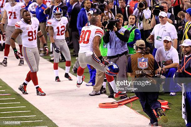 Victor Cruz of the New York Giants celebrates with his teammates after catching a two yard touchdown pass from Eli Manning in the first quarter...