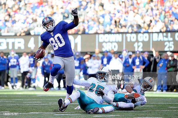 Victor Cruz of the New York Giants leaps over Will Allen of the Miami Dolphins on his way to scoring a 25 yard touchdown in the fourth quarter...