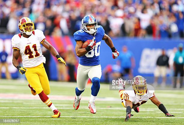 Victor Cruz of the New York Giants runs after a catch for the winning touchdown as Madieu Williams and Josh Wilson of the Washington Redskins give...