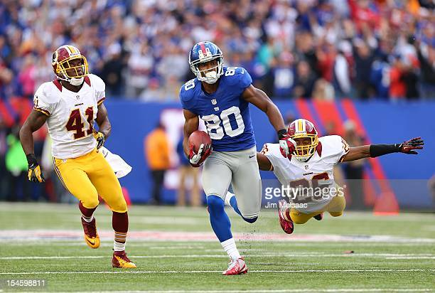 Victor Cruz of the New York Giants runs in a touchdown reception late in the fourth quarter against Madieu Williams and Josh Wilson of the Washington...