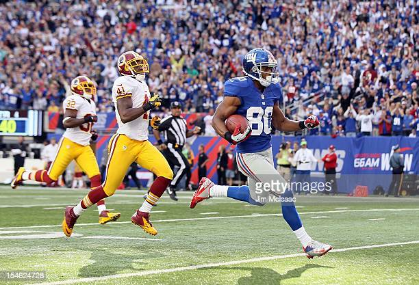 Victor Cruz of the New York Giants runs in a touchdown reception late in the fourth quarter against Madieu Williams of the Washington Redskins at...