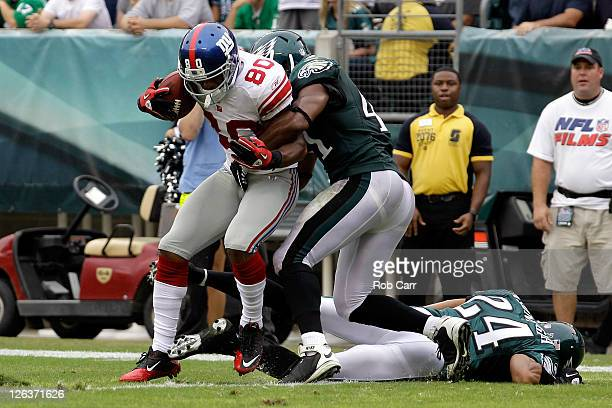 Victor Cruz of the New York Giants scores a touchdown against Jarrad Page of the Philadelphia Eagles and Nnamdi Asomugha during the game at Lincoln...