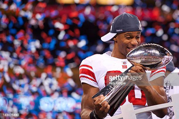 Victor Cruz of the New York Giants shows emotion while holding the Vince Lombardi trophy after winning Super Bowl XLVI against the New England...
