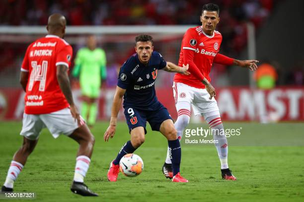 Victor Cuesta of Internacional struggles for the ball with Angelo Henriquez of Universidad de Chile during a match between Internacional and...
