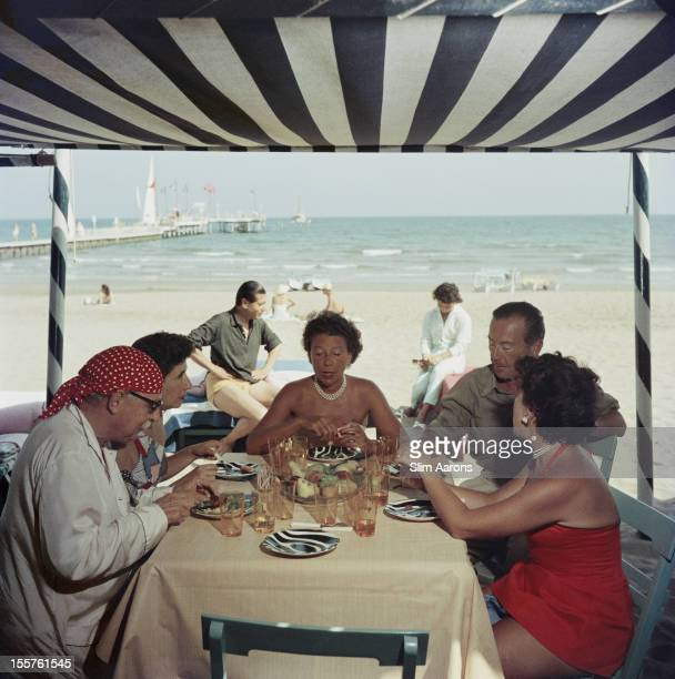 Victor Cunard, Contessa Alberta Foscari, Contessa Anna Maria Cicogna, Jack Rodrigue and Maria Salata Phillips sitting around a table on The Lido,...