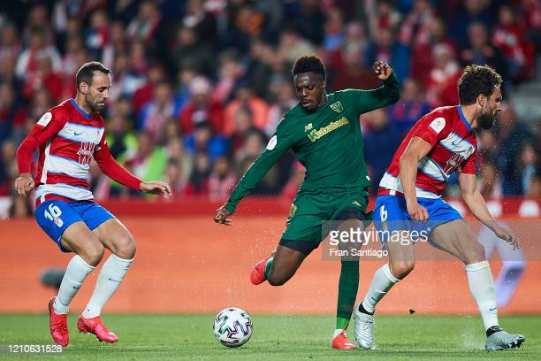 Victor Diaz and German Sanchez of Granada CF compete for the ball with Inaki Williams of Athletic Club during the Copa del Rey semifinal 2nd leg...