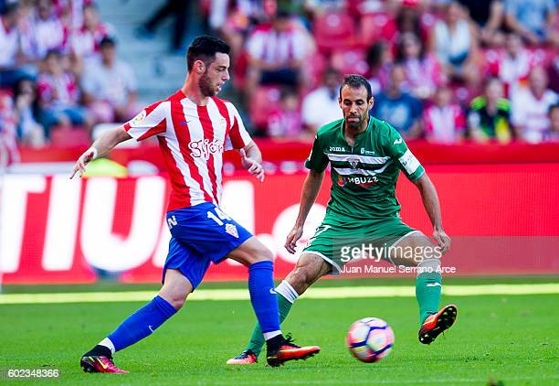 Victor Diaz of Club Deportivo Leganes duels for the ball with Jorge Franco 'Burgui' of Real Sporting de Gijon during the La Liga match between Real...