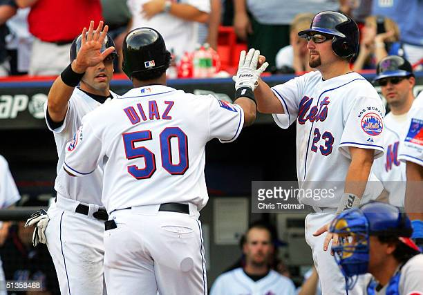 Victor Diaz of the New York Mets is congratulated by teammates Eric Valent and Jason Phillips on his game-tying three-run home run in the bottom of...