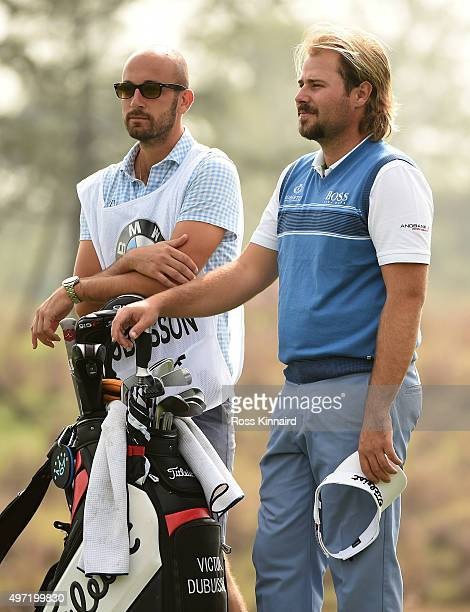 Victor Dubuisson of France and his caddie stand for a minutes silence as a mark of respect for those killed in the Paris bombings during the final...