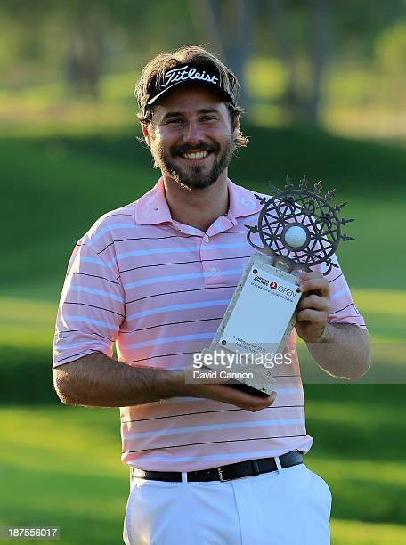 Victor Dubuisson of France holding the trophy after he had finished on a total of 24 under par and a two stroke victory over Jamie Donaldson during...