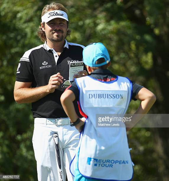 Victor Dubuisson of France looks onwith his caddie during a practice round ahead of the DD Real Czech Masters at Albatross Golf Resort on August 26...