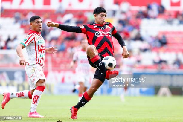 Victor Guzman of Club Tijuana, competes for the ball with Maximiliano Salas of Necaxa during the 11th round match between Necaxa and Club Tijuana as...