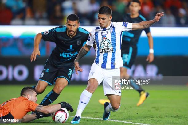 Victor Guzman of Pachuca struggles for the ball with Tiago Volpi of Queretaro during the 16th round match between Pachuca and Queretaro as part of...