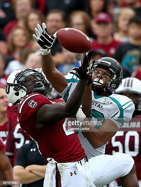 Victor Hampton of the South Carolina Gamecocks breaks up a pass to Seun Olukoju of the Coastal Carolina Chanticleers during their game at...